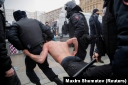 Riot police detain a protester during January 23, 2021, rally for Navalny.