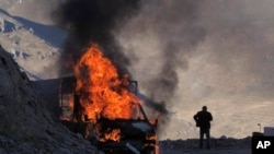 A man stands near his burning car along the road to a mountain pass, near the border between Nagorno-Karabakh and Armenia, on Sunday, Nov. 8, 2020.