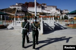 Paramilitary police officers swap positions during a change of guard in front of Potala Palace in Lhasa, during a government-organized tour of the Tibet Autonomous Region on October 15, 2020. Thomas Peter/Reuters