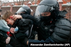 Police officers detain a young demonstrator during a protest near the Matrosskaya Tishina prison where Alexey Navalny is being held, in Moscow, Russia, on Sunday, Jan. 31, 2021.