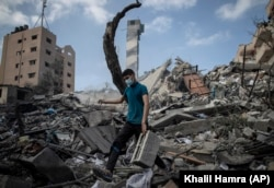 A Palestinian man inspects the damage of a six-story building which was destroyed by an early morning Israeli airstrike in Gaza City, Tuesday on Tuesday, May 18, 2021.