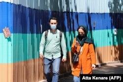 Iranians wearing protective masks walk on a sidewalk in the capital Tehran, April 12, 2021.