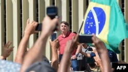 President Jair Bolsonaro speaks in a protest in Brasilia against quarantine and social distancing measures to fight the coronavirus outbreak, on April 19, 2020.