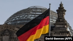 The German flag flys outside the Reichstag, the building which houses the Bundestag (the German lower house of parliament) in Berlin, February 24, 2021.