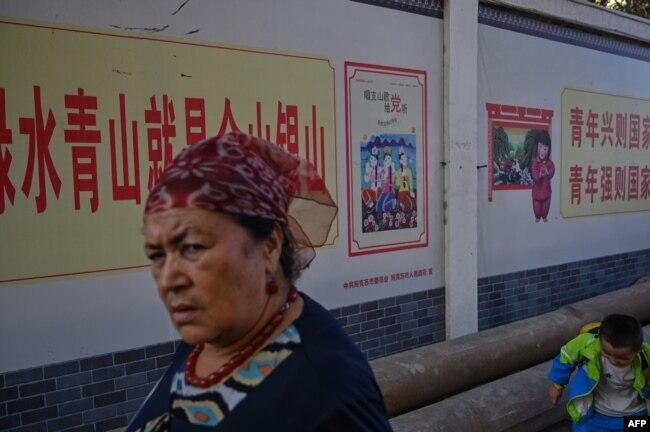 This photo taken on September 11, 2019 shows a woman walking in an ethnic Uighur neighborhood in Aksu in the region of Xinjiang. (Photo by HECTOR RETAMAL/AFP)