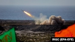 IRAN -- Iranian military fires a missile targeting a mock-up of U.S. aircraft carrier in the strategic Strait of Hormuz, July 28, 2020.