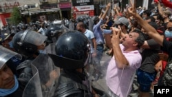 Members of Tunisian security forces face off with anti-government demonstrators during a rally in front of the parliament building in the capital Tunis on July 25, 2021.