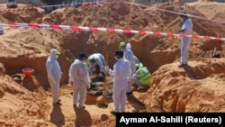 Members of the Government of National Accord's (GNA's) missing persons bureau, exhume bodies in what Libya's internationally recognized government officials say is a mass grave, in Tarhouna city, Libya.