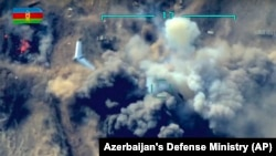 NAGORNO KARABAKH -- In this photo taken from video released by the Azerbaijan's Defense Ministry on Thursday, Oct. 1, 2020, an unmanned aerial vehicle flies over a site where Azerbaijan's forces attack the Armenian army's artillery gun during fighting in