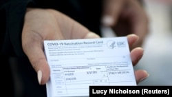 A medical worker holds Pfizer coronavirus disease (COVID-19) vaccination cards at a mobile vaccination drive for essential food processing workers at Rose & Shore, Inc., in Vernon, Los Angeles, California, U.S., March 17, 2021.