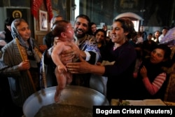 ROMANIA -- Priest Nicolae Ganga (C) baptizes a child during a mass Orthodox baptism ceremony at a church in the Bora neighborhood in Slobozia, November 29, 2012.